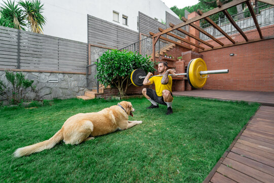 Athletic male in sportswear doing clean and jerk exercise with barbell during workout in backyard with fluffy dog