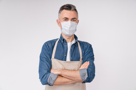 Confident caucasian mature barista in medical protective mask against Covid 19 with arms crossed isolated over white background