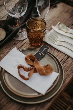 From above of guest seating card placed on plate on banquet wooden table served for wedding celebration