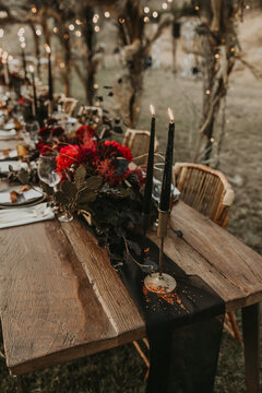 Wooden table served with plates and decorated with flowers in garden for wedding party