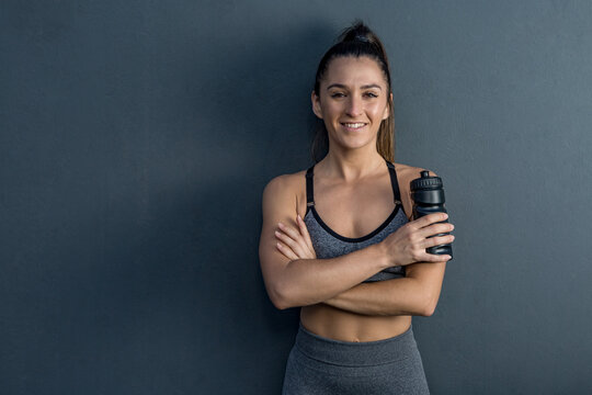 Smiling fit sportswoman in activewear standing with plastic bottle of water on gray background and looking at camera