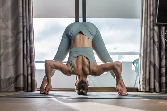 Full body of female doing Wide Legged Forward Bend asana for stretching muscles of body during yoga training