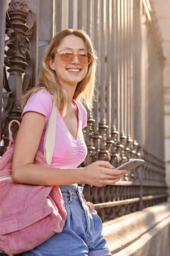 Side view of positive teenage female with backpack smiling brightly while scrolling mobile phone leaning on metal fence