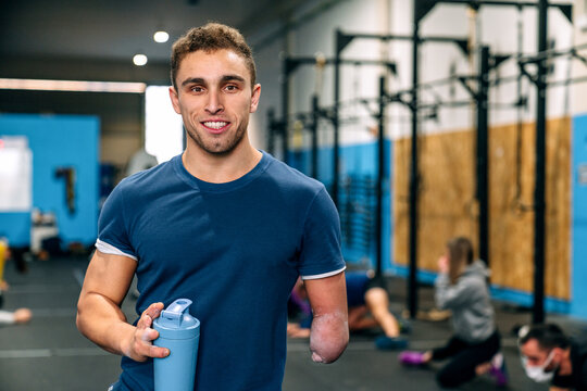 Young disabled happy male athlete in sportswear holding bottle of water while looking at camera during workout near unrecognizable partners in gymnasium