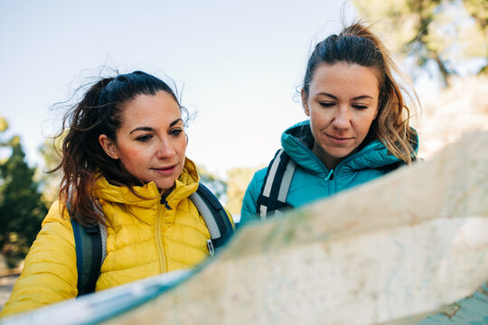 Traveling women standing near car on road with paper map and orientating while looking for direction during vacation