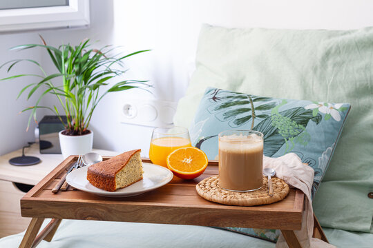 Cup of coffee and homemade sponge cake placed on wooden tray with glass of fresh orange juice prepared for breakfast in bedroom