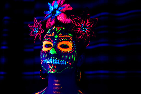 Anonymous female in multicolored masquerade mask with flowers on head looking at camera on Halloween night