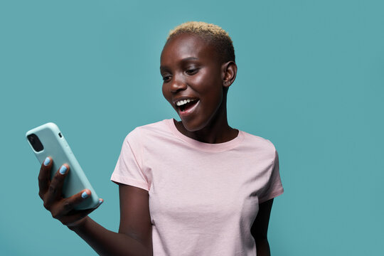 Expressive beautiful African American female with short hair and bright manicure browsing on smartphone against blue background