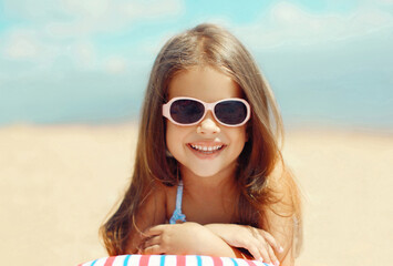 Summer close up portrait of happy smiling little girl child lying on sand beach