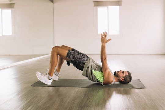 Side view of muscular young bearded male athlete lying on mat near mirror and doing Glute Bridge March exercise while training alone in spacious light studio