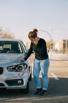 Full body of upset young female driver in casual outfit having phone conversation while standing on road and inspecting damages on modern car after crash