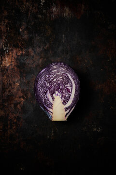 Top view of a lilac cabbage cut in half on rustic wooden background