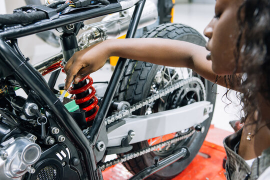 Side view of African American female mechanic with wrench fixing custom motorbike while working in workshop