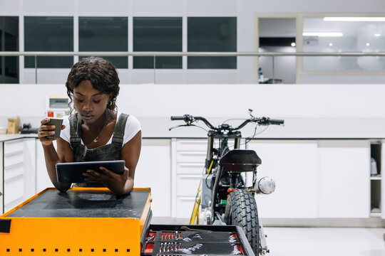 Serious African American female technician in uniform using tablet and drinking coffee while leaning on tool cabinet in modern motorbike workshop