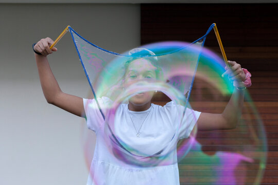 Cheerful young African American female teenager with dark hair in white t shirt playing with big colorful soap bubbles and having fun standing on street near wooden wall