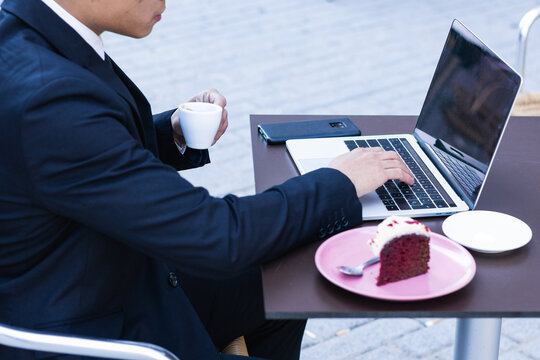 Asian male entrepreneur in classy suit sitting at table with laptop in cafe and eating sweet cake while having coffee break during work