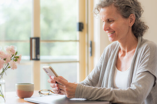 Close up of middle aged woman with grey hair looking at mobile phone and smiling (selective focus)