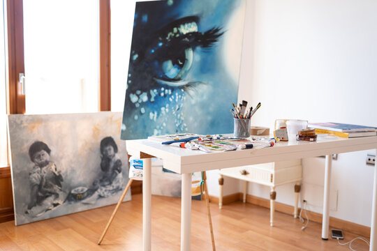 Art studio interior with collection of painted pictures and paint brushes in glass on table in daylight