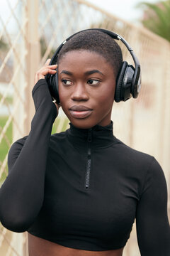 Crop young dreamy black female listening to music from wireless headphones while looking away in daylight