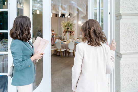 Wedding planners, organizers, event decorators, florists. Young beautiful women, girls in stylish suits at entrance to restaurant. Business meeting, negotiations,signing contract with client,customer