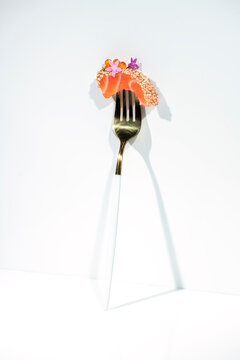 Piece of tasty salmon sashimi decorated with caviar and herbs on fork against white background