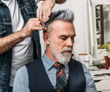 Crop anonymous barber styling hair of elegant well dress bearded middle aged male customer sitting on chair and looking away in modern studio