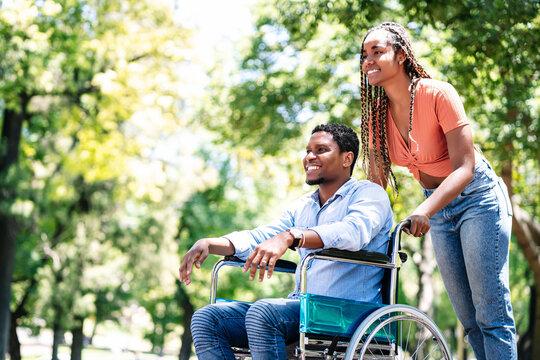 Man in a wheelchair enjoying a walk with his girlfriend.