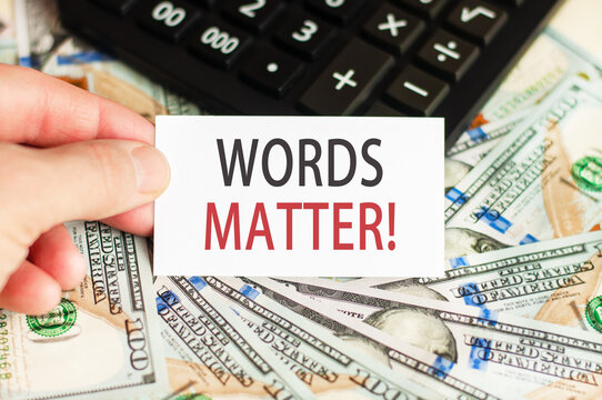 On the table are bills, a bundle of dollars and a sign on which it is written - WORDS MATTER. Finance and economics concept.