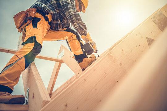 Carpenter Working on Wooden House Frame