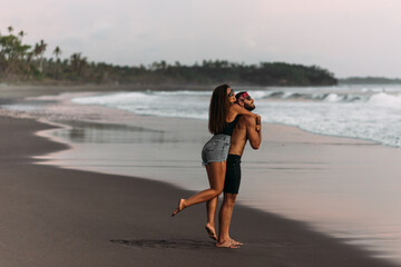 A man and a woman have fun at sunset by the sea. Happy couple on the beach. Tanned couple having...