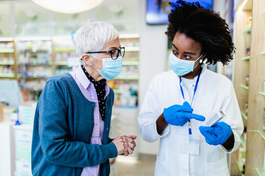 Professional Black female pharmacist talking with senior customer in modern drugstore. They are wearing face protective masks for protection from Coronavirus.