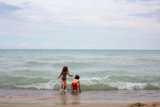 Young girl and boy on the beach of Lake Michigan with her shoes in her hands