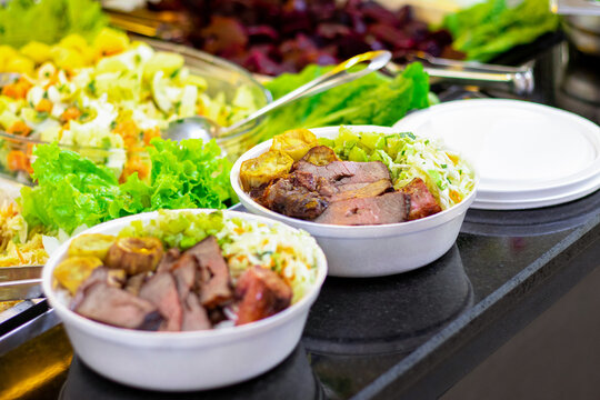 Marmitex with meat, rice, beans, sweet potatoes and coleslaw  in a white bowl - packed lunch - Brazilian Food.