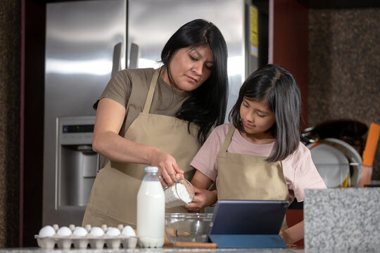 Mexican mother and daughter cooking in kitchen looking the recipe on a tablet