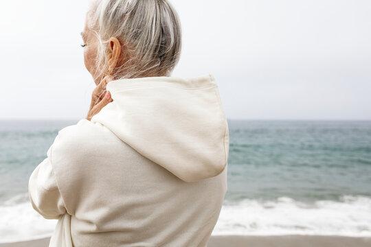 Senior woman in hoodie relaxing at the beach