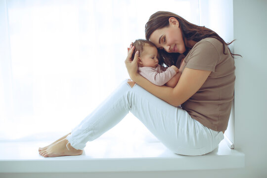 A young mother is holding her newborn baby. Mother of a nursing baby. Mother breastfeeding her baby. The family is at home. Portrait of a happy mother and child. High quality photo.