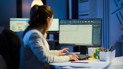 Woman architect matching digital plans from pc with blueprints working in start-up business office overtime. Designer using cad software to design a 3D concept of buildings creating late at night