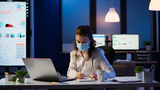 Manager woman with face mask working overtime in new normal business office checking team project, taking notes, analysing financial documents sitting at desk late at night during global pandemic