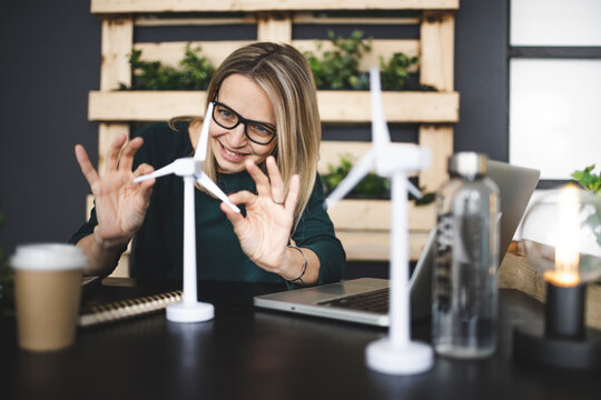 pretty, young and blond woman with stylish, modern black glasses sits in a sustainable office and works with pinwheel wind turbine models