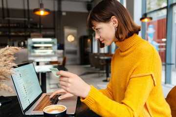 Happy redhead girl using credit card while working with laptop in cafe