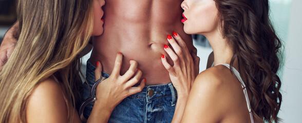 Obraz Sexy women playing on naked man abs banner - fototapety do salonu