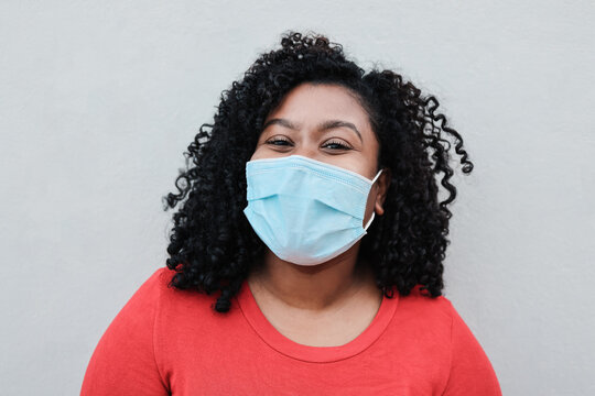 Young african woman smiling on camera while wearing safety mask during coronavirus outbreak - Focus on face