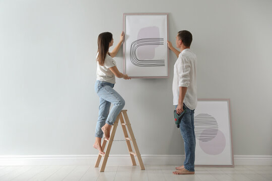 Couple hanging picture on wall together in room. Interior design