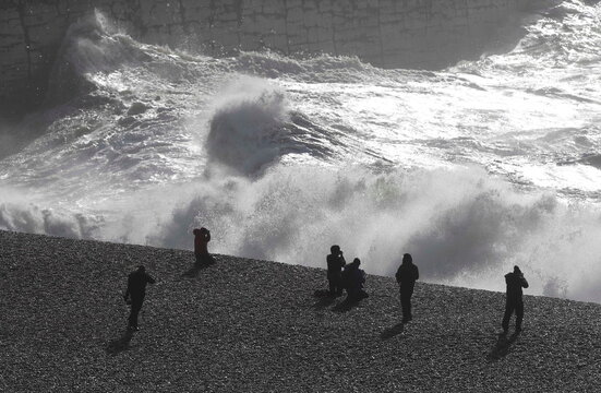People watch as large waves hit the harbour wall at Newhaven