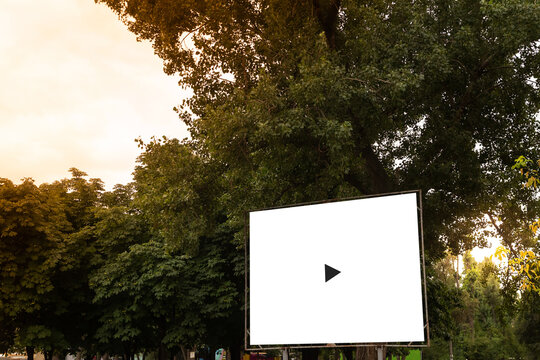 Open air cinema or theater, outdoors movie. Large movie screen, film playing on the sunset background