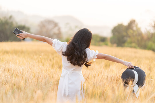 Back view of young long hair woman in white dress standing alone stretching her arms out and holding her hat and phone in the golden color barley field during golden hour