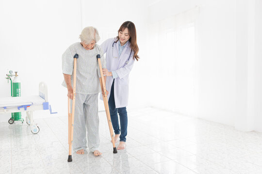 asian old patient learning to use crutches with female doctor, walk training and rehabilitation, elderly health promotion