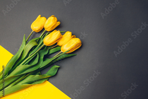 Spring yellow flowers. Bouquet of tulips on grey background. Present, gift for Mother's day. Space