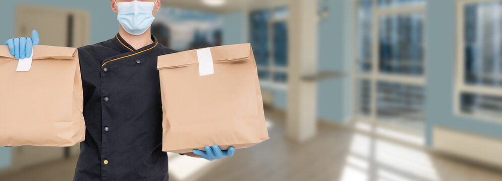 Delivery man holding cardboard packages in medical rubber gloves and mask. copy space. Fast and free Delivery. Online shopping and Express delivery . Quarantine
