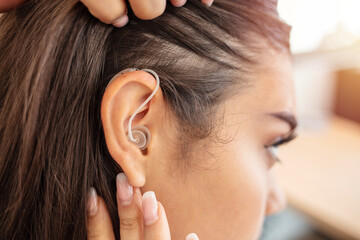 Fototapeta Woman adjusting hearing aid indoors. Close up of a hearing aid on the woman's ear. Deaf woman wearing hearing aid. Digital hearing aid in woman's ear